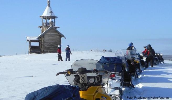 Halt am Unesco-Welterbe: Eine Gruppe von Motorschlittenfahrern macht Rast an einer der zahlreichen Holzkirchen auf der Insel Kischi im Onegasee
