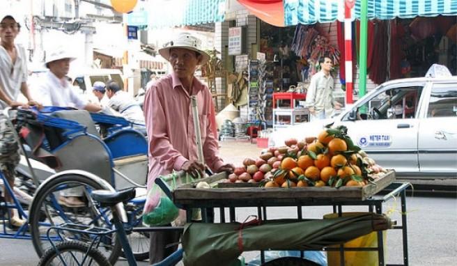 Ein Fruchtverkäufer im alltäglichen Getümmel.