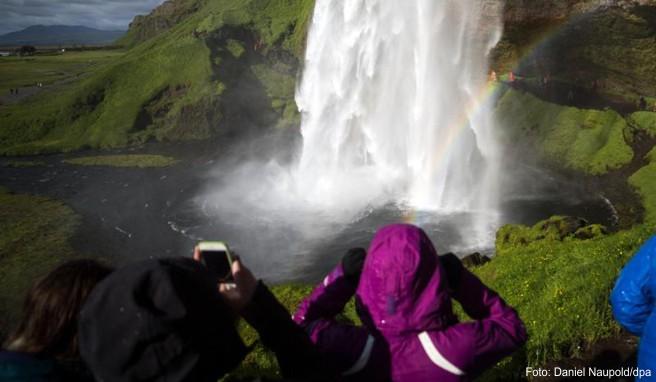 Touristen schauen sich am den Wasserfall »Seljalandsfoss« in der Gemeinde Rangarping eystra in Island an. Nach wachsenden Touristenmassen droht in Island die Stimmung gegenüber Urlaubern zu kippen.